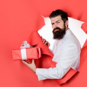 man ripping through the wall holding a present