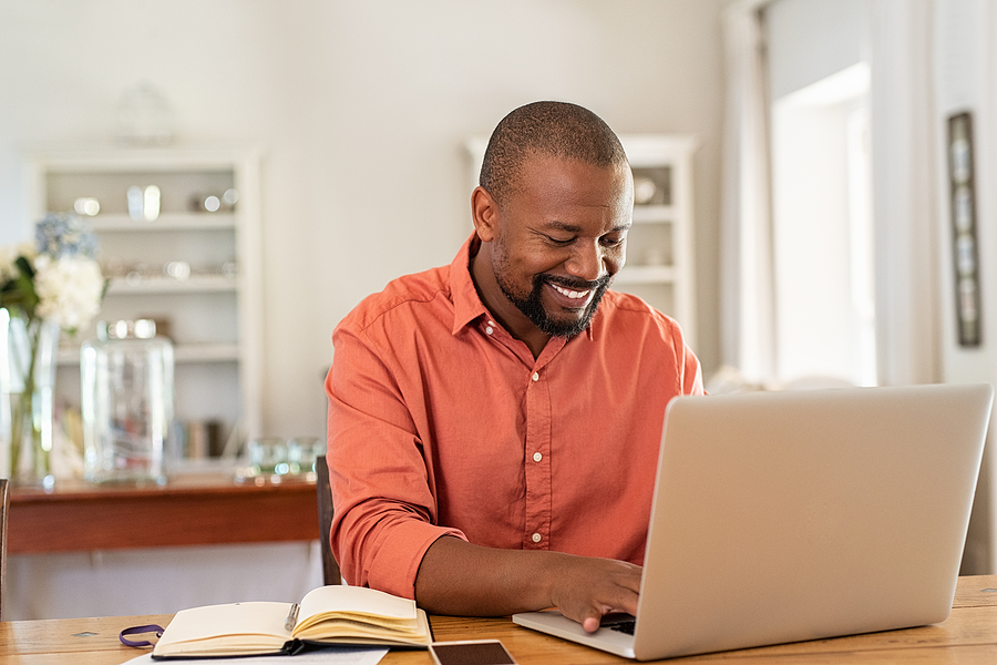 man sitting in front of computer smiling knowing his website is backed up and secure